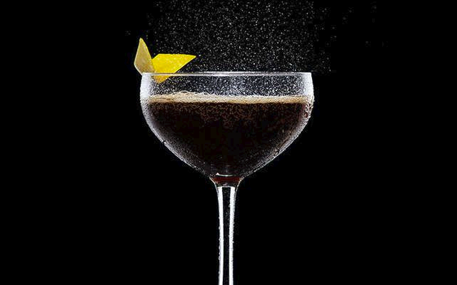 Gin Cola in martini glass fizzing with lemon zest twist garnish