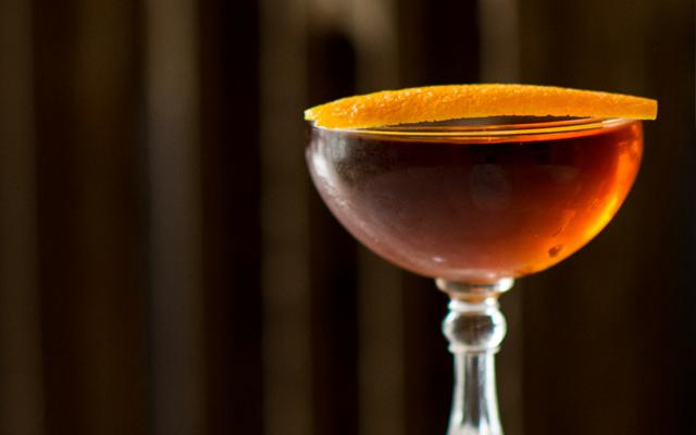 Martinez Red Orange cocktail in martini glass with orange twist garnish
