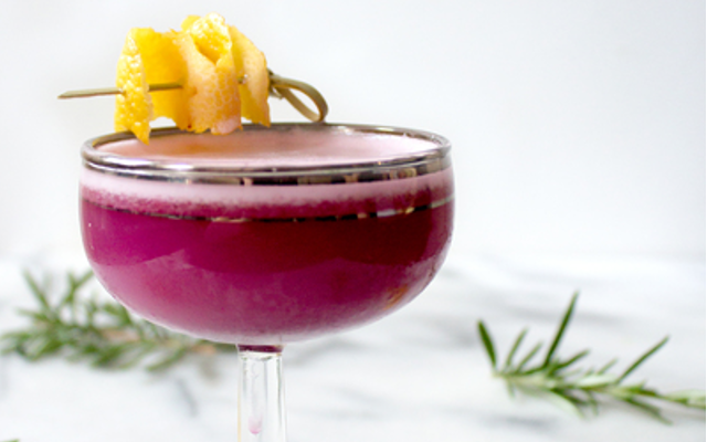 Purple blueberry gin sour with lemon garnish