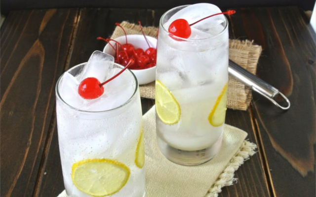 tom collins gin cocktail with lemon and cherries garnish