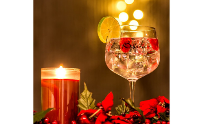 Batch gin perfect serve with raspberries and lime, scented christmas candel