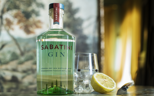 Sabatini gin bottle and lemon next to a g&T