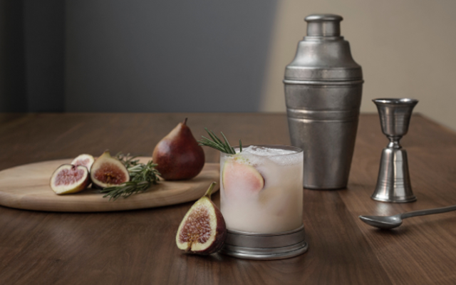 Cocktail with cocktail shaker and fig garnish