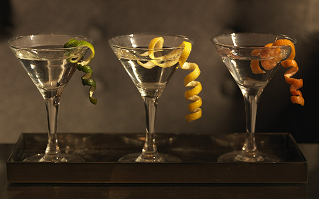 three martini cocktails with garnish citrus twists