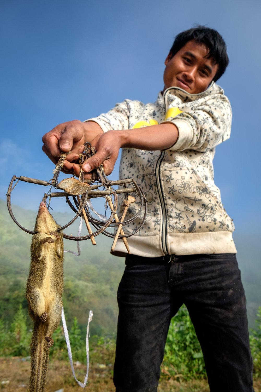 Un homme exhibant avec fierté la réussite de son piège.