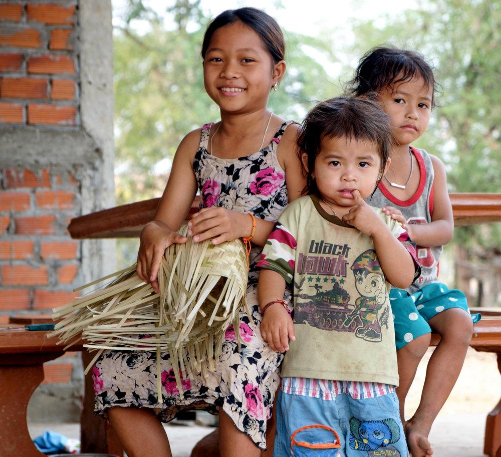 Jeune fille tressant un panier avec ses soeurs.