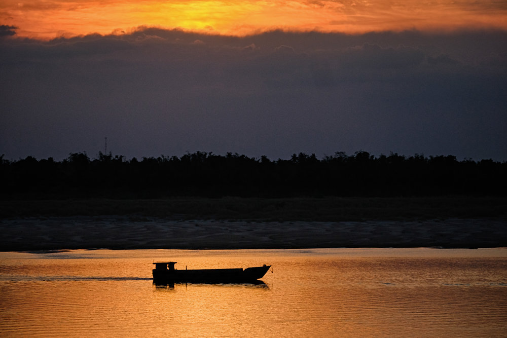 Pirogue au coucher du soleil sur le Mékong.