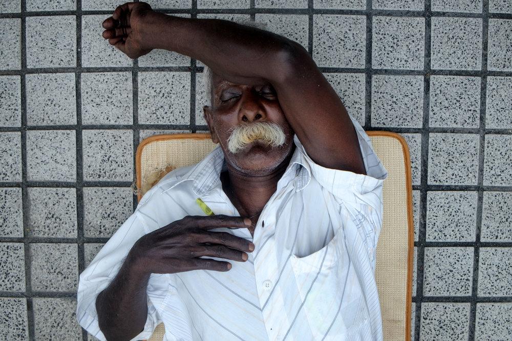Un Indien faisant la sieste directement sur le trottoir.