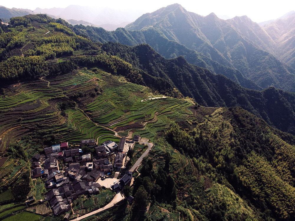 Un village perché entre la falaise et les champs de riz, dans la Chine rurale.