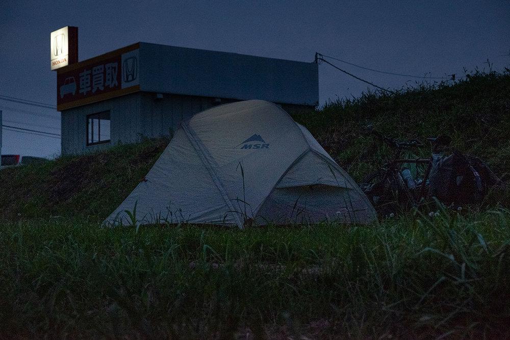 Camper dans la cour d'un concessionnaire automobile au Japon.