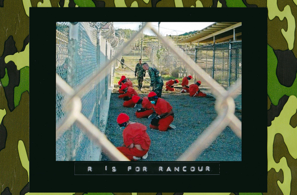 Detainees in orange jumpsuits sit in a holding area under guard by military police at Camp X-Ray inside U.S. Naval Base Guantánamo Bay, Cuba, during their processing into the temporary detention facility, Jan. 11, 2002. (Photo: U.S. Navy)