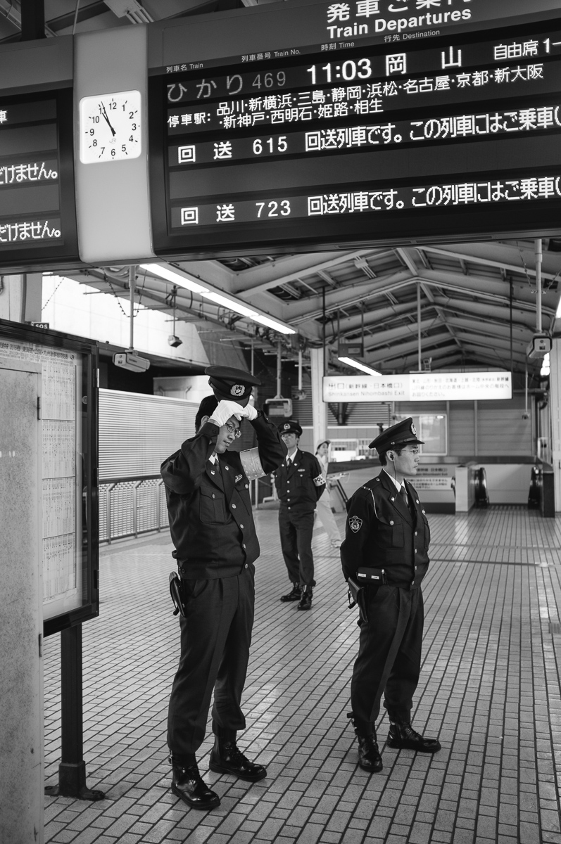 The police looking bored at the arrival of the bullet train.