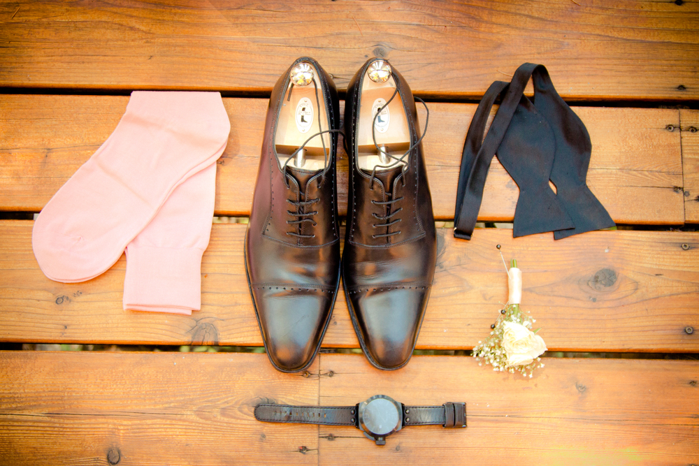 Groom's accessories laid out on wood at Rockwater Secret cove elopement and wedding spot