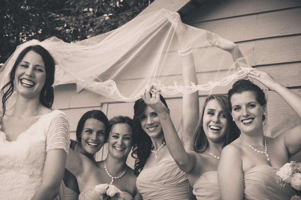 Bridesmaids playing with veil at Rockwater Secret cove elopement and wedding spot