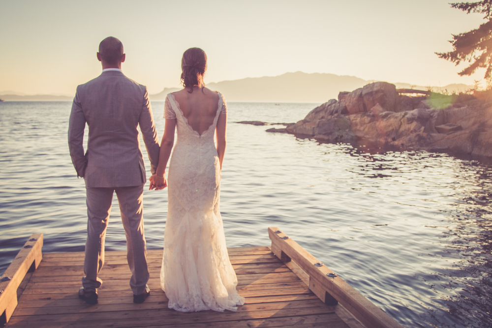 Bride and groom holding hands watching sunset from dock at Rockwater Secret cove elopement and wedding spot
