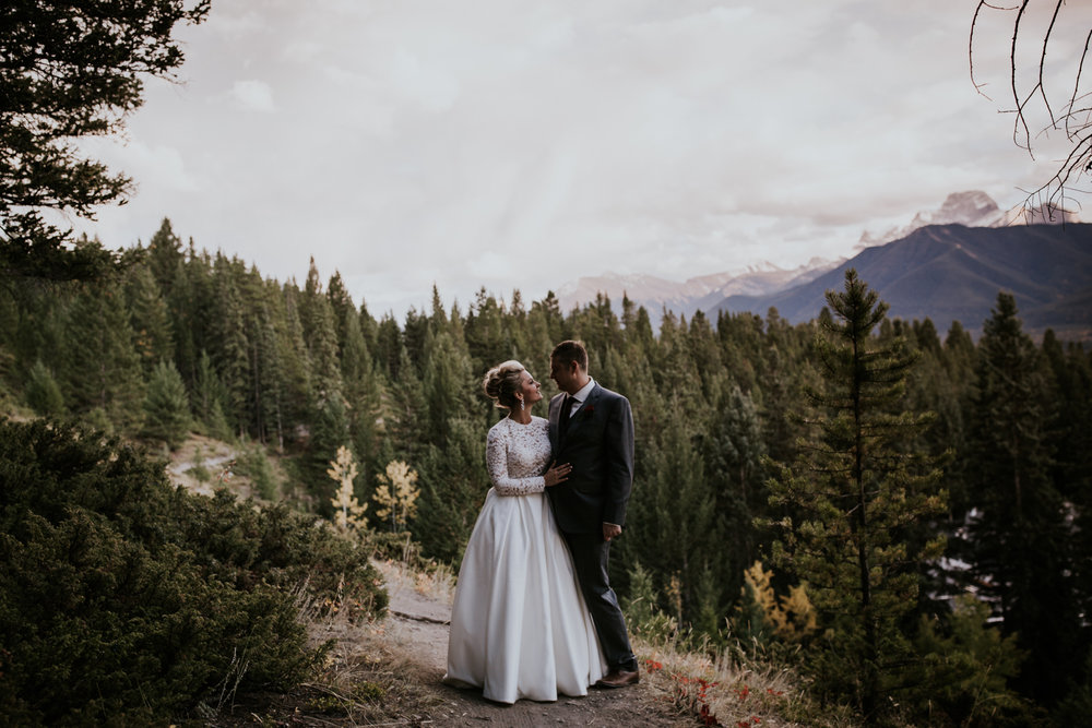 Bride and groom dancing at sunset overlooking Canmore