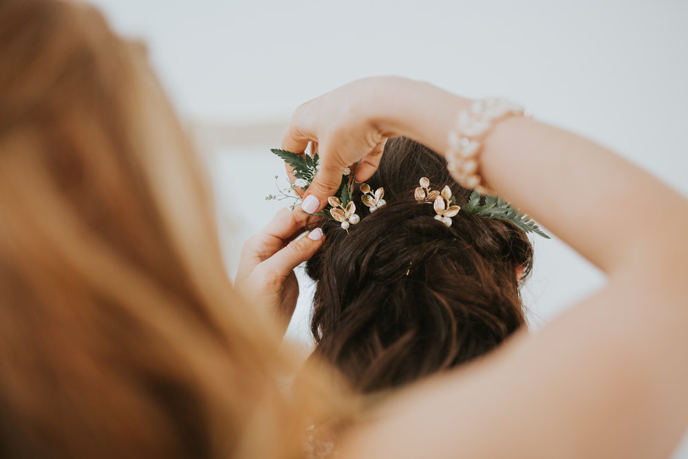 Bride having finishing touches done on hair with greenery at Starling Lane Winery