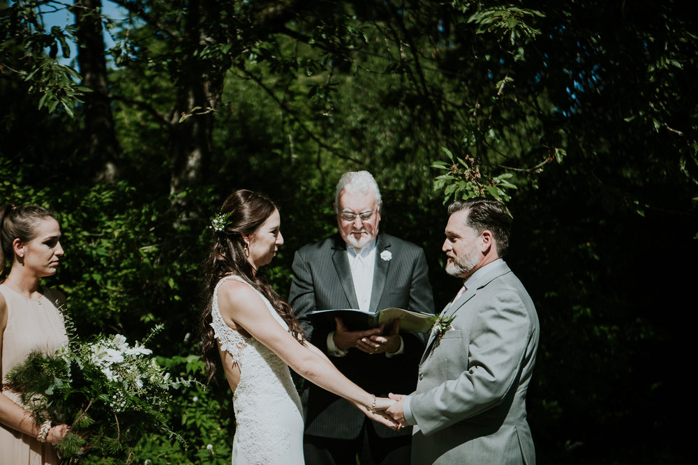 Bride and groom holding hands during ceremony at Starling Lane winery