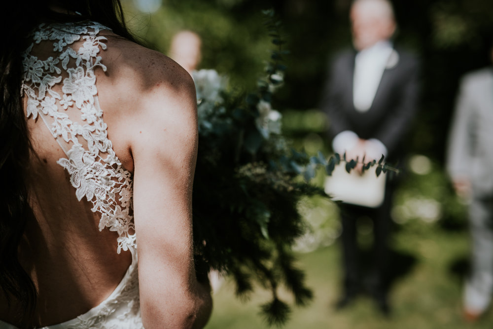 Close up of brides bouquet and back of bride as she walks down aisle at Starling Lane winery