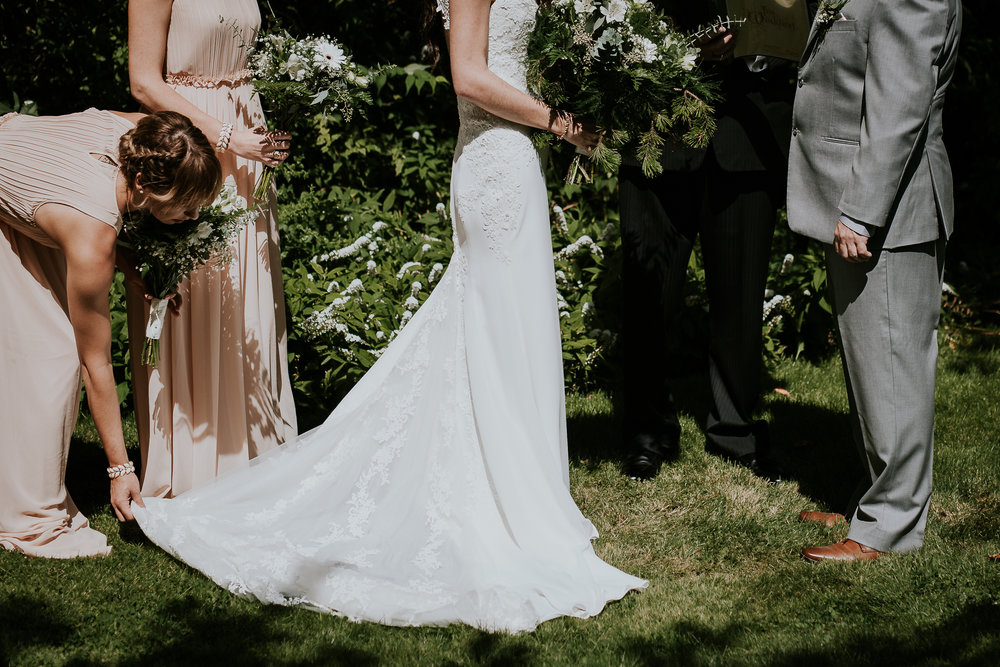 Bridesmaid fixing brides dress during ceremony at Starling Lane winery