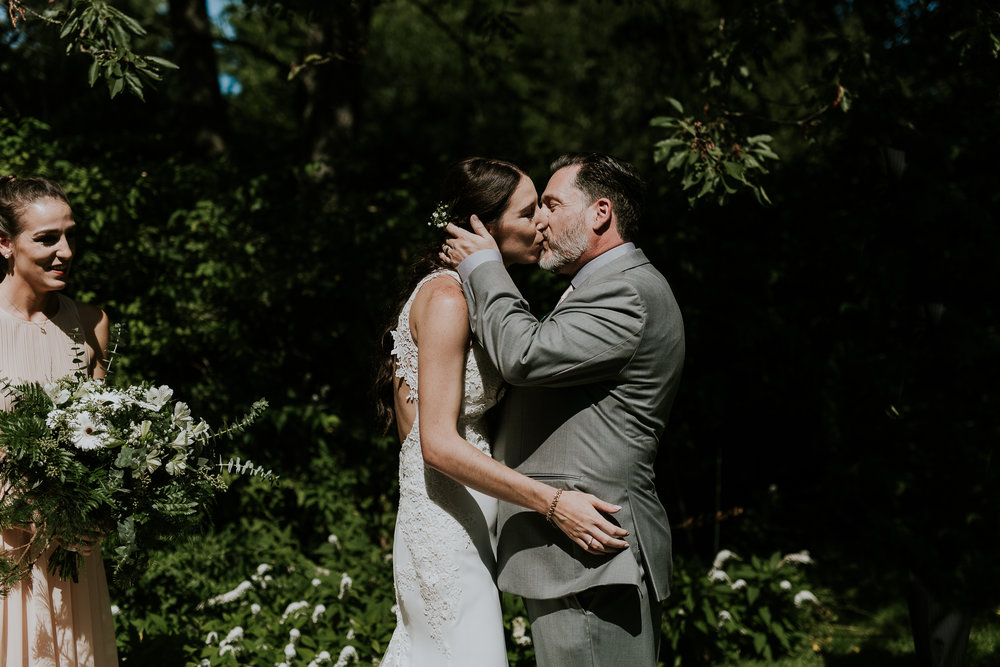 Bride and groom sharing first kiss at vineyard wedding on Vancouver Island
