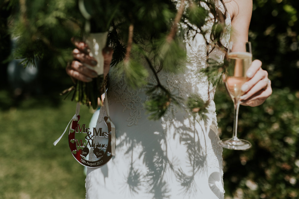 Bride holding bouquet and Mr & Mrs sign after wedding ceremony at vineyard near victoria Bc