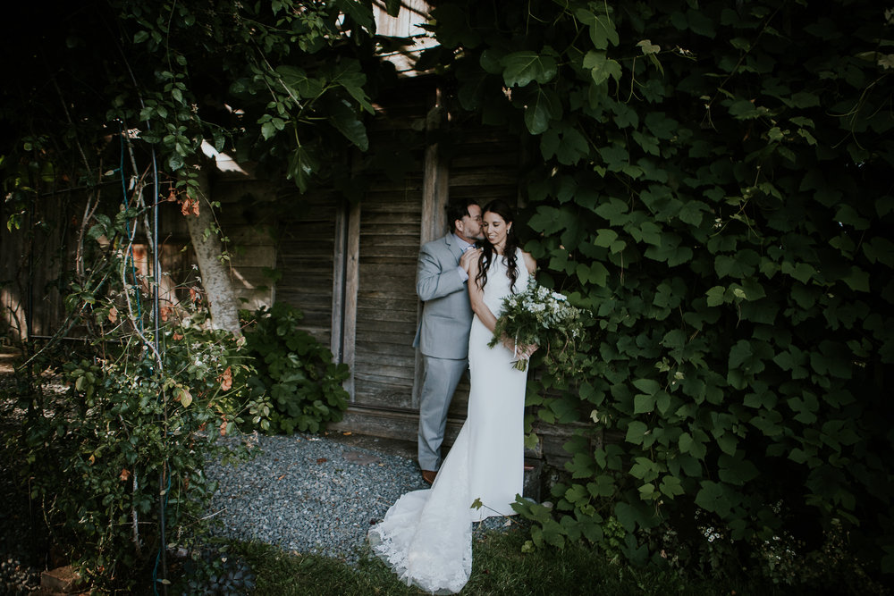 Bride and groom standing under climbing vines at vineyard wedding on Vancouver Island