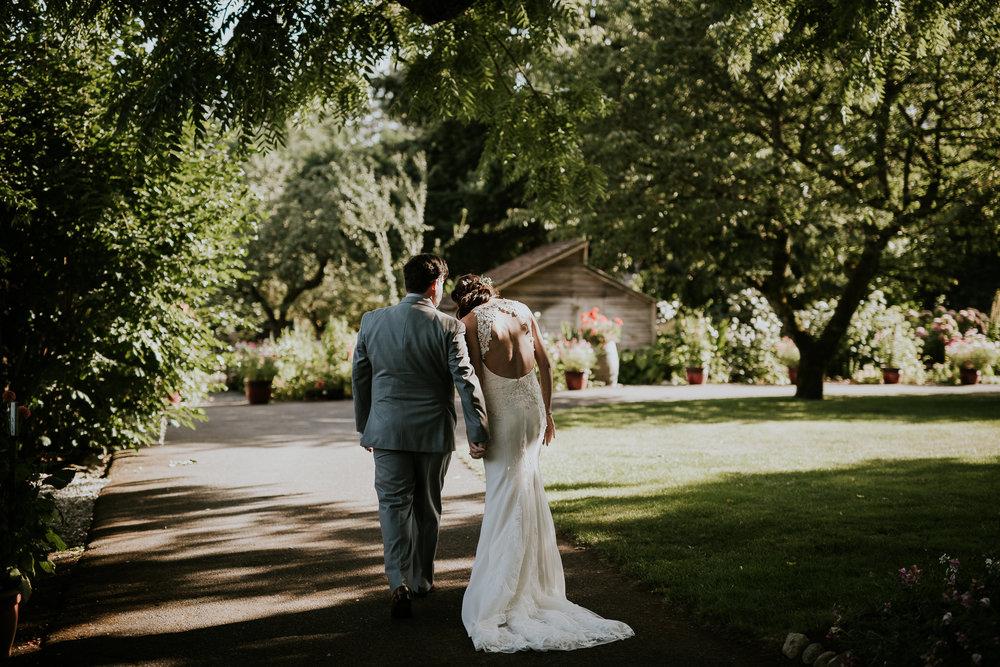 Bride and groom holding hands walking through vineyard wedding on Vancouver Island