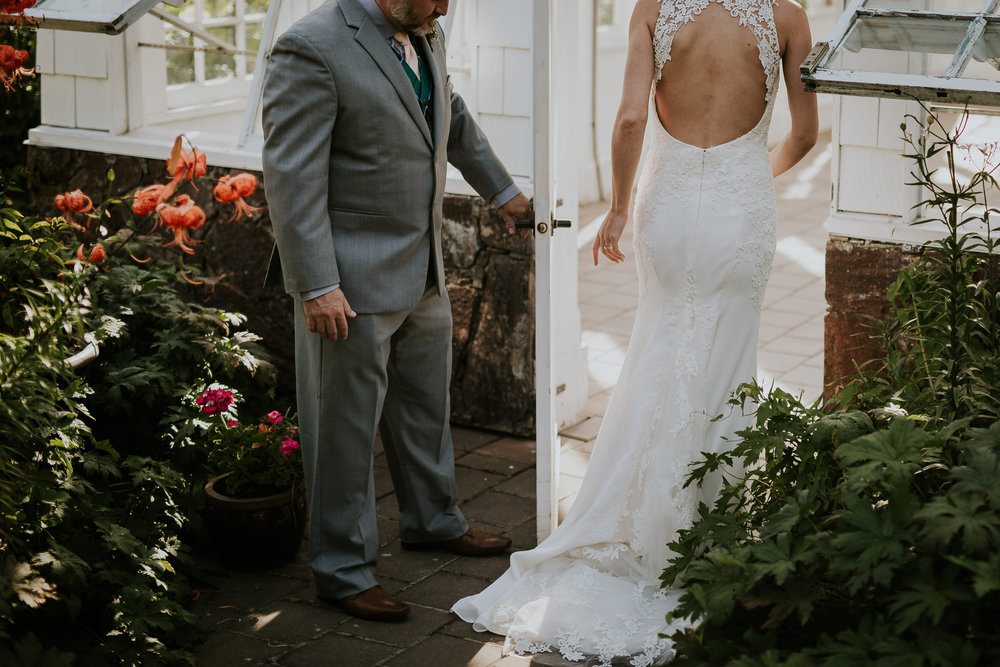 Groom holding brides dress while she walks into greenhouse for wedding photos near Victoria BC