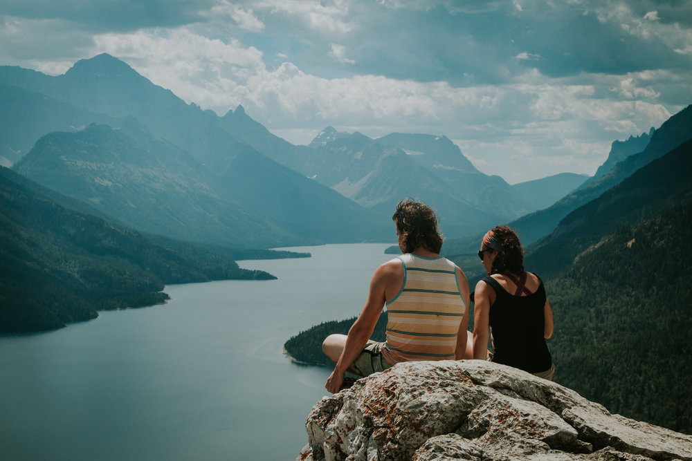 Bride and groom enjoying view of town of Waterton and Waterton Lakes from Bears Hump hike after adventurous elopement in Waterton National Park