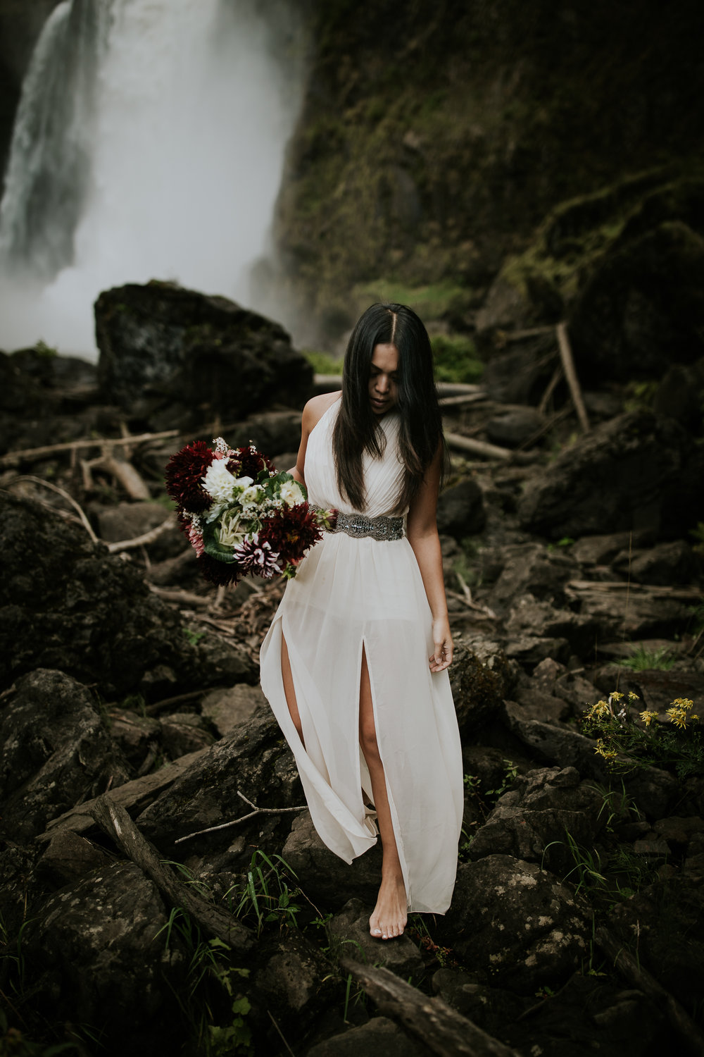 Barefoot bride climbing over rocks at Snoqualmie Falls elopement