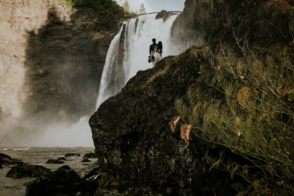 Bride and groom climbing over large rock in front of Snoqualmie Falls for adventurous elopement
