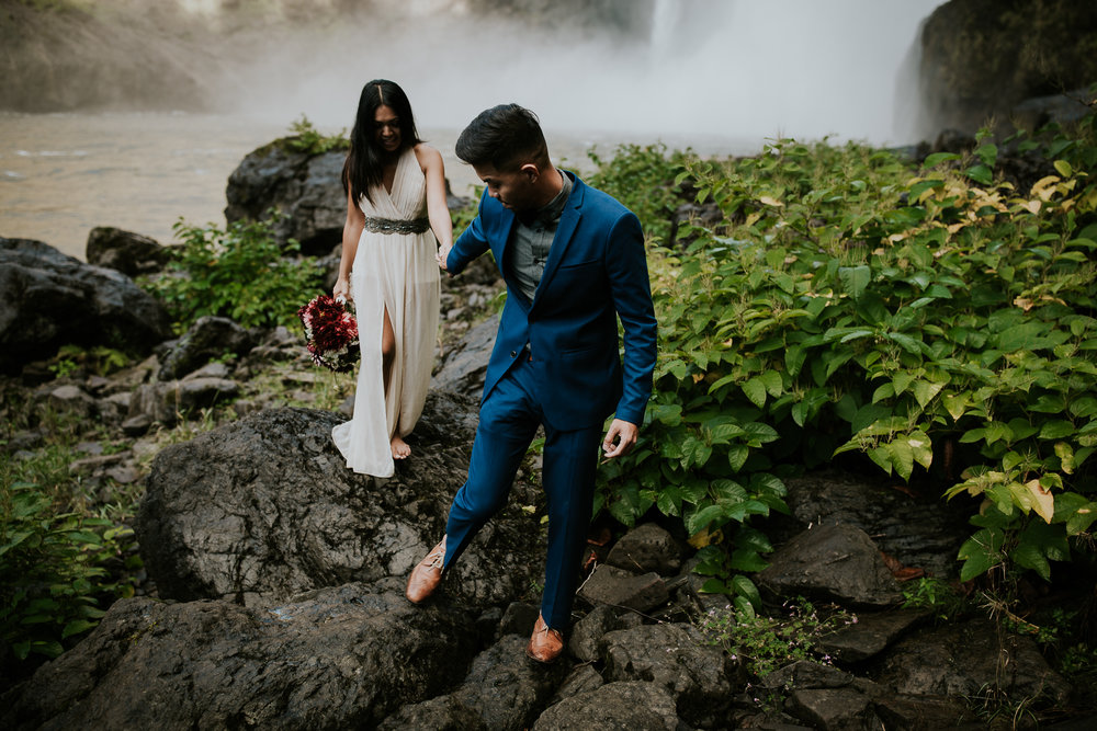 Groom leading adventurous bride over rocks in front of Snoqualmie falls
