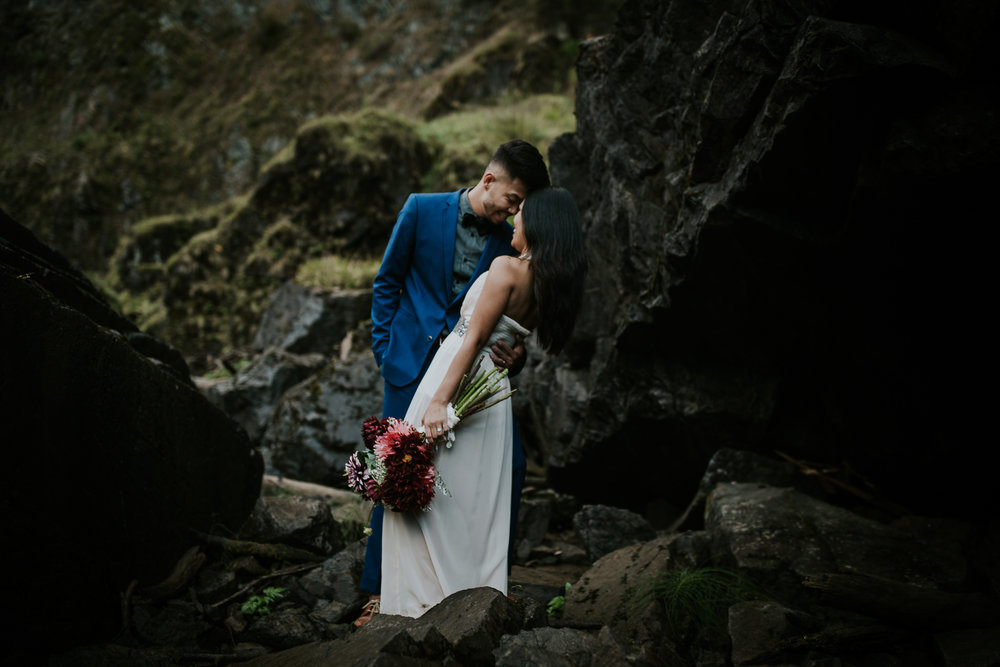 Bride and groom leaning in for a kiss and smiling during waterfall elopement near Seattle
