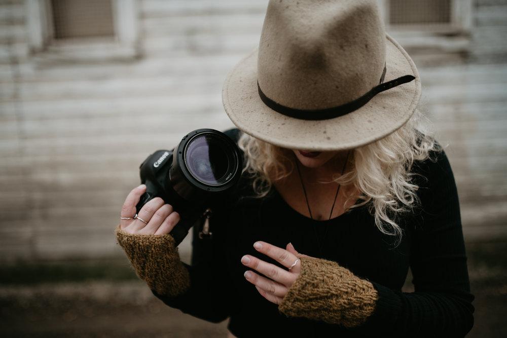 Calgary-based Alberta travel wedding photographer holding camera in urban wedding venue.