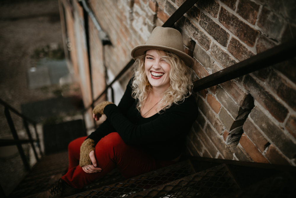Romantic, adventurous, documentary style wedding photographer sitting on stairs wearing a hat and fall colours.
