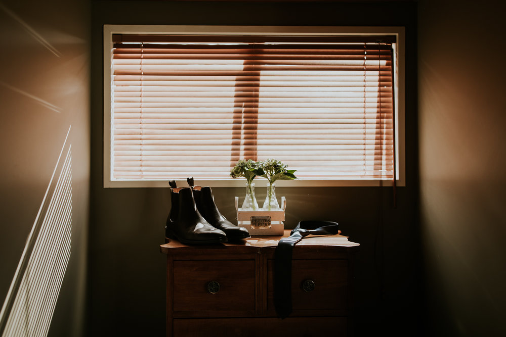 Groom's shoes, tie and watch sitting on dresser before getting ready for wedding.