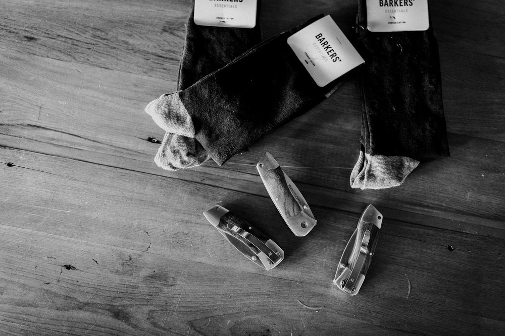 Grooms gifts for groomsmen of knives and socks displayed on floor