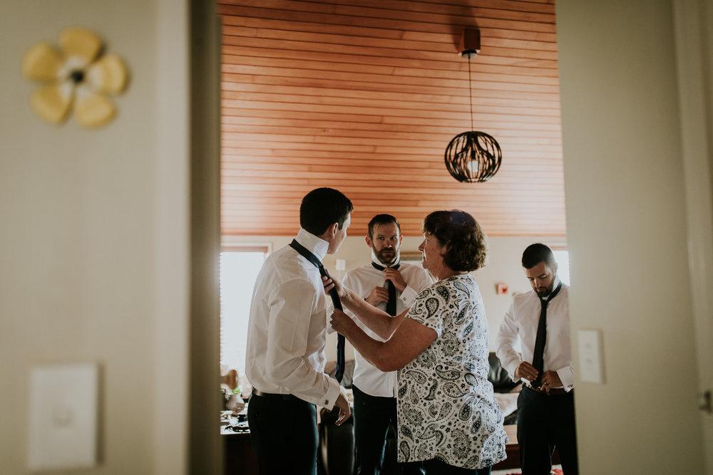 Mother of the groom helping groomsmen tie their ties.