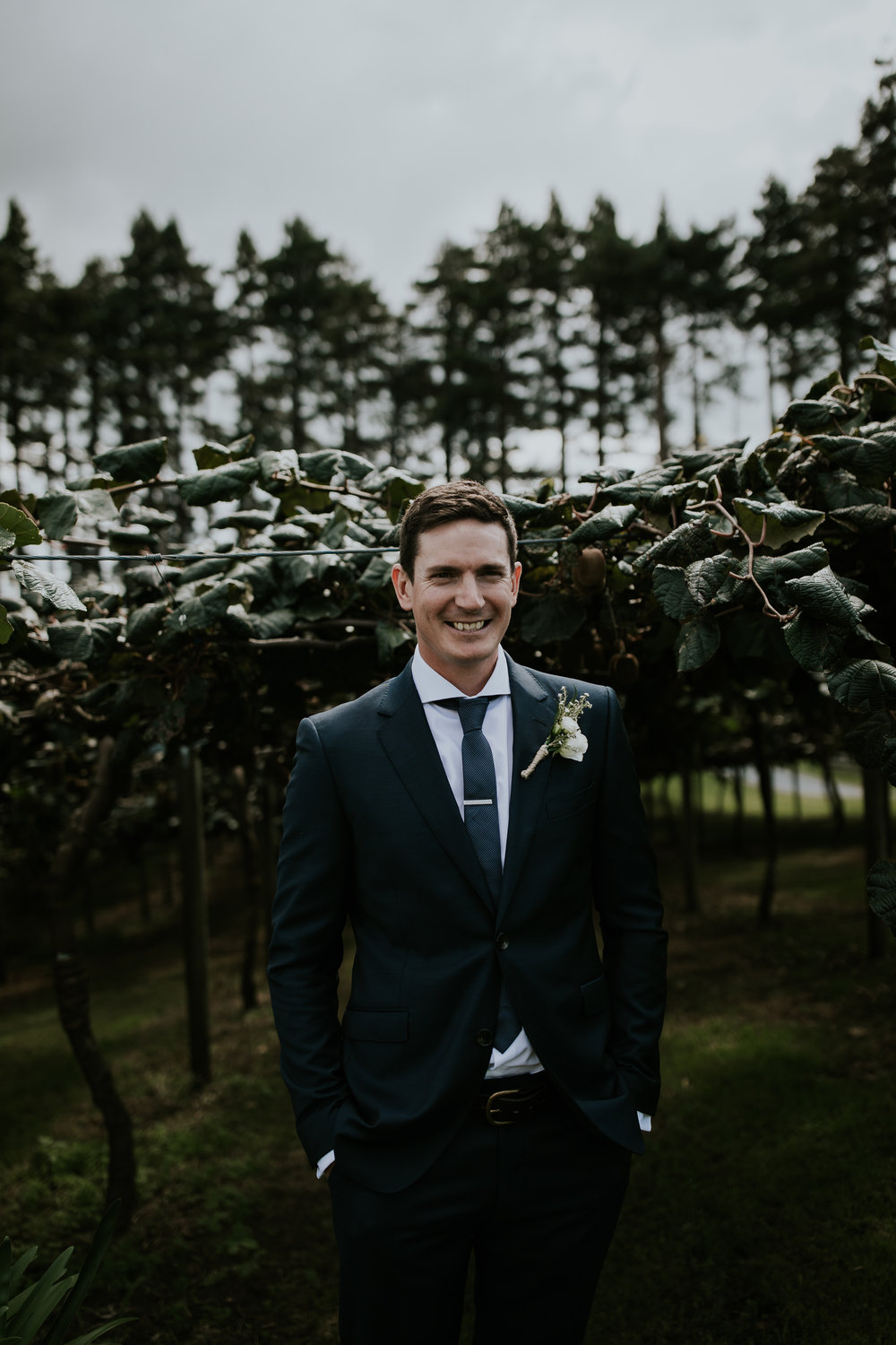 Portrait of the groom standing in front of kiwi orchard before his wedding day