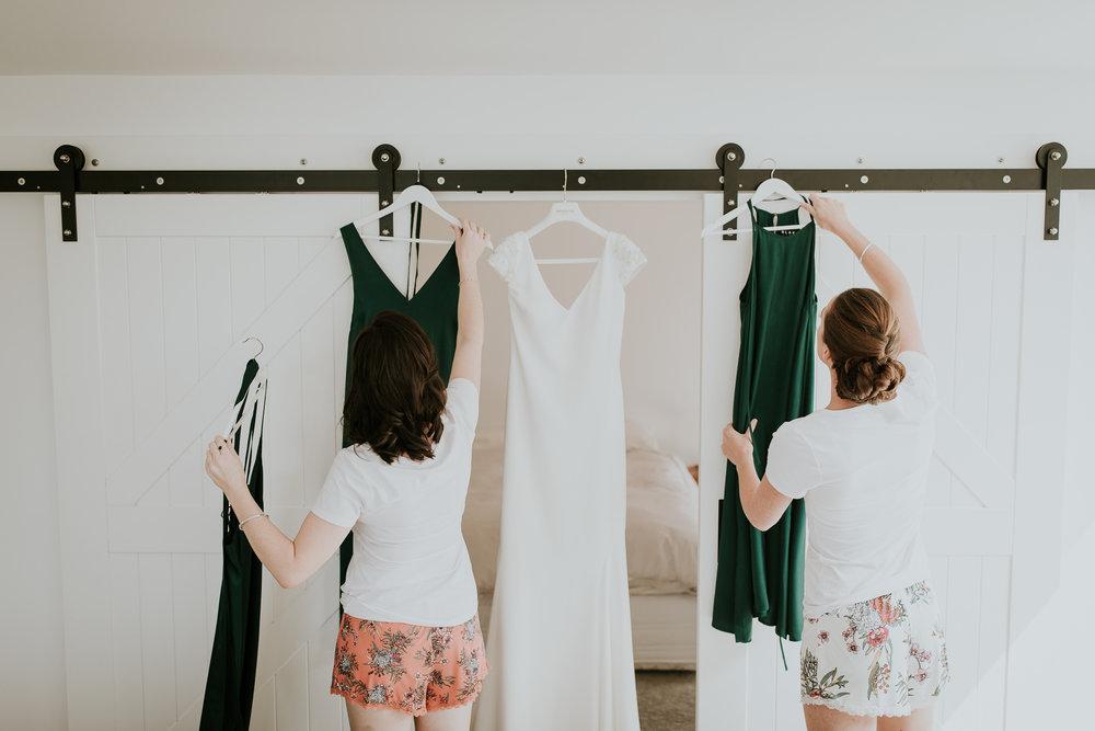 Bridesmaids hanging brides dress and bridesmaids dresses for detail shot
