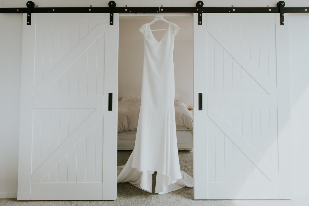 Brides dress hanging in between farm doors at elegant farm wedding in New Zealand