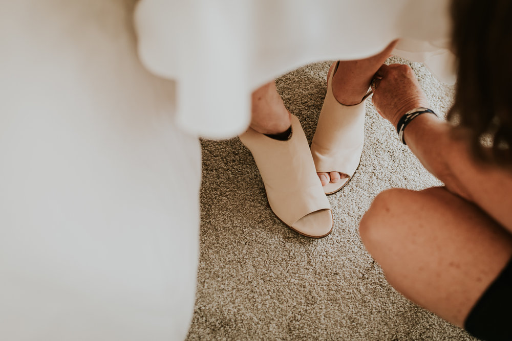 Bride putting on shoes with the help of mother of the bride