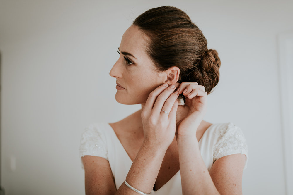 Bride putting on the finishing touches of earrings in bridal suite