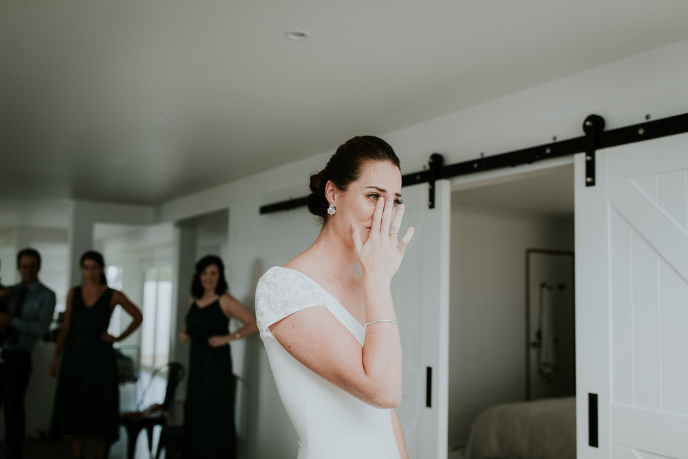 Bride wiping a tear away after revealing her dress to her family