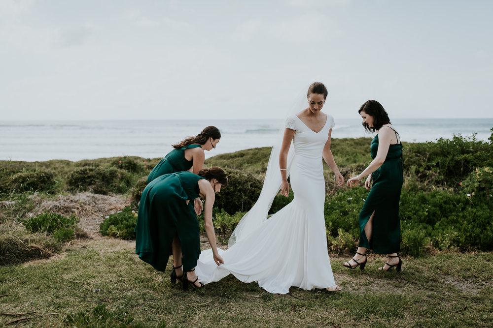 Bridesmaids helping bride straighten gown at beachside wedding in New Zealand