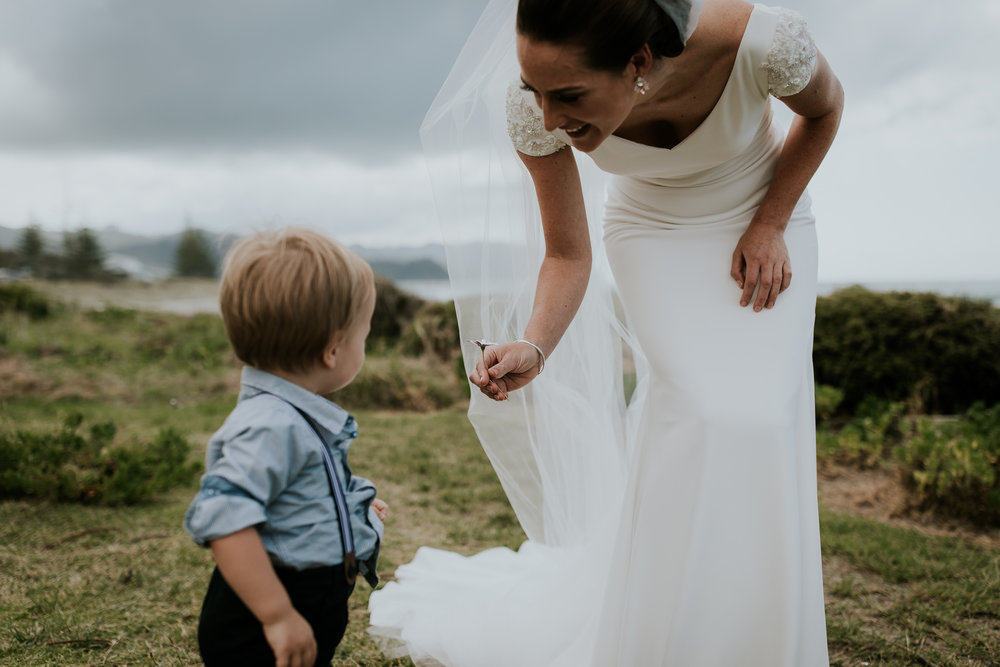 Brides nephew handing her a flower on her wedding day