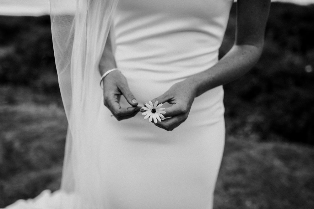Black and white of bride holding white daisy on her wedding day in her wedding dress