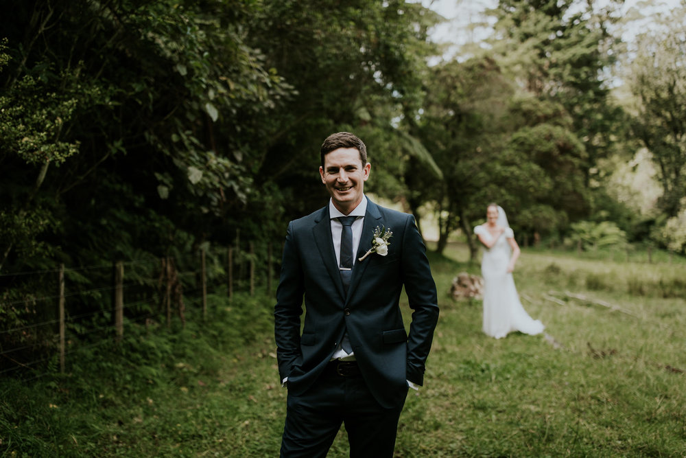 Groom waiting in field for bride during first look in New Zealand wedding