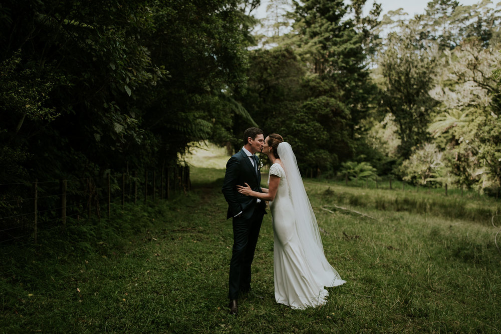 New Zealand bride and groom sharing first kiss in farmers field after emotional first look
